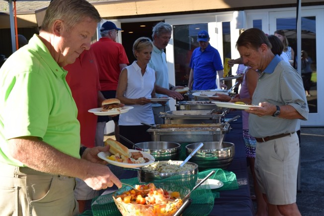 Golf tournament patrons eating at table